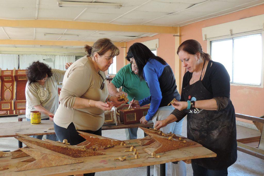 La artista Corrales a cargo de la obra junto a colaboradoras locales en la restauracion del retablo
